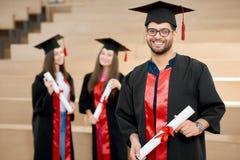 Menino de sorriso feliz que mantém o diploma da universidade fotografia de stock royalty free