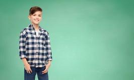 Menino de sorriso na camisa quadriculado e nas calças de brim Foto de Stock