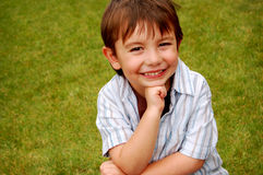 Menino de sorriso na grama Imagens de Stock