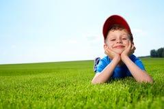 Menino de sorriso na grama Imagem de Stock Royalty Free