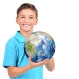 Menino de sorriso na terra guardando ocasional do planeta nas mãos Fotografia de Stock Royalty Free