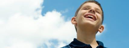 Menino de sorriso nas nuvens Fotos de Stock