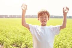 Menino de sorriso no campo na manhã ensolarada do verão Imagens de Stock