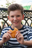 Menino de sorriso novo com um penteado elegante e um hamburguer Imagens de Stock Royalty Free