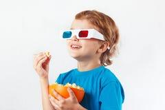 Menino de sorriso novo em vidros estereofônicos que come a pipoca Imagem de Stock Royalty Free