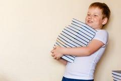 Menino de sorriso de oito anos que guarda muitos livros fotos de stock