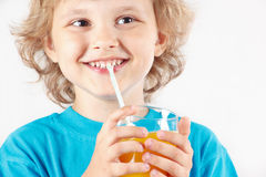 Menino de sorriso pequeno que bebe um sumo de laranja fresco imagens de stock royalty free