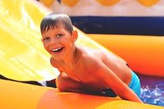 Menino de sorriso perto do waterslide foto de stock