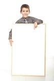 Menino de sorriso que aponta à bandeira em branco Fotografia de Stock Royalty Free