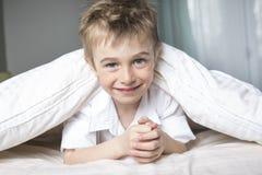 Menino de sorriso que esconde na cama sob uma cobertura ou uma coberta branca Imagens de Stock Royalty Free