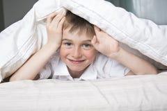 Menino de sorriso que esconde na cama sob uma cobertura ou uma coberta branca Fotos de Stock Royalty Free
