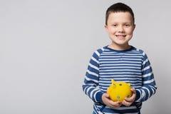 Menino de sorriso que guarda um mealheiro amarelo em suas mãos, encontradas frontal, no conceito das economias e na finança foto de stock
