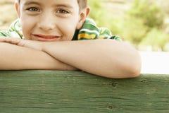 Menino de sorriso que inclina-se em trilhos de madeira Imagens de Stock