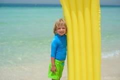 Menino de sorriso que joga na praia com colchão de ar Fotos de Stock