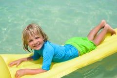 Menino de sorriso que joga na praia com colchão de ar Fotografia de Stock Royalty Free