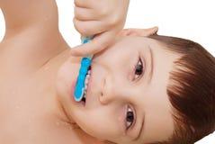 Menino de sorriso que limpa seus dentes Fotografia de Stock