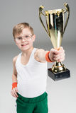Menino de sorriso que mostra o cálice do ` s do campeão no cinza fotos de stock royalty free
