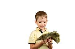Menino de sorriso que olha uma pilha de 100 dólares americanos b Fotos de Stock Royalty Free