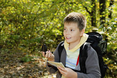 Menino de sorriso que orienteering na floresta Fotos de Stock