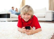 Menino de sorriso que presta atenção à tevê encontrar-se no assoalho Imagem de Stock