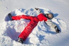 Menino de sorriso que senta-se na neve no parque imagem de stock royalty free