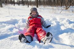 Menino de sorriso que senta-se na neve no parque imagens de stock