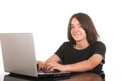 Menino de sorriso que usa o computador portátil Fotografia de Stock