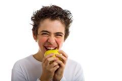 Menino de sorriso que vai morder uma maçã amarela imagem de stock royalty free