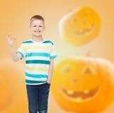 Menino de sorriso sobre o fundo das abóboras Fotografia de Stock Royalty Free