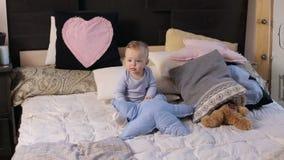 Menino de um ano bonito pequeno que senta-se na cama em uma cobertura macia vídeos de arquivo