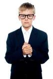 Menino de vista pensativo que levanta com as mãos clasped foto de stock royalty free