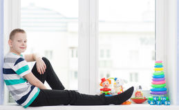 Menino de Yang que senta-se perto da janela Fotos de Stock
