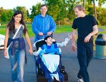Menino deficiente na cadeira de rodas que anda no parque junto com a família Fotos de Stock