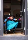 Menino deficiente na porta da rua da abertura da cadeira de rodas Imagens de Stock
