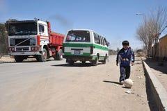 Menino desconhecido que joga com uma bola na estrada de Oruro Imagens de Stock Royalty Free