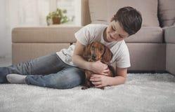 Menino despreocupado que abraça seu cão com amor fotos de stock royalty free