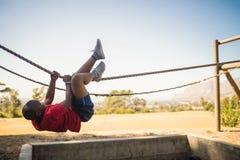 Menino determinado que cruza a corda durante o curso de obstáculo fotografia de stock royalty free