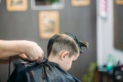 menino do Little que obtém o corte de cabelo por Barber While Sitting In Chair no barbeiro  Imagens de Stock