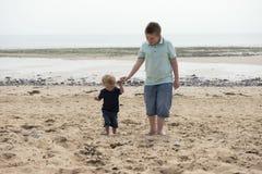 Menino do adolescente de onze anos com o irmão do bebê da criança de dois anos em uma praia Fotos de Stock