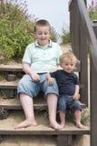 Menino do adolescente de onze anos com o irmão do bebê que senta-se em etapas Fotografia de Stock Royalty Free