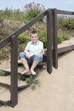Menino do adolescente de onze anos que senta-se em etapas em uma praia em um dia ensolarado Fotografia de Stock Royalty Free