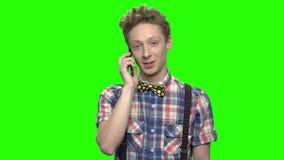 Menino do adolescente na camisa quadriculado que fala com telefone video estoque