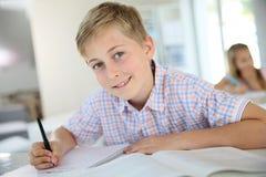 Menino do adolescente no wiritng da classe Foto de Stock Royalty Free