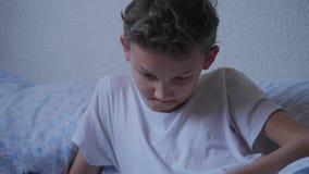 Menino do adolescente que conversa na rede social na tabuleta, sorrindo vídeos de arquivo