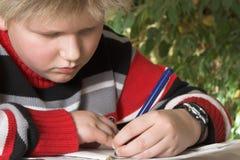 Menino do adolescente que escreve seu exercício Fotografia de Stock Royalty Free