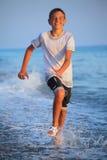 Menino do adolescente que funciona na roupa molhada na praia Fotografia de Stock Royalty Free