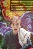 Menino do adolescente que kneeing na frente de um grafitti da flor Imagem de Stock