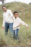 Menino do African-American que puxa o pai em dunas de areia imagem de stock royalty free