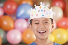 Menino do aniversário que veste uma coroa na frente dos balões imagem de stock royalty free