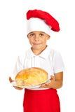 Menino do cozinheiro chefe que dá o pão Fotos de Stock